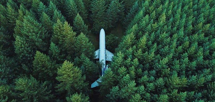 Drohnenaufnahme einer Boeing 727 im Wald. Das Flugzeug wird von Bruce Campbell bewohnt, welcher es zwischen den Bäumen zusammengesetzt hat.